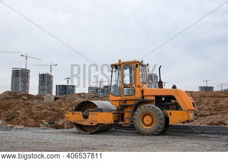Vibro Roller Soil Compactor Leveling Soil At Construction Site. Excavator And Vibration Single-cylin