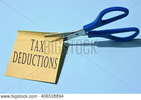 Scissors That Cut Yellow Notepad With Tax Deductions Text