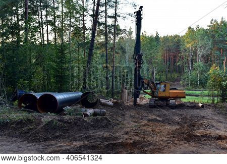 Vibrating Hydraulic Hammer In Forest Area. Hydraulically Driven Free-fall Hammer For Impact Driving