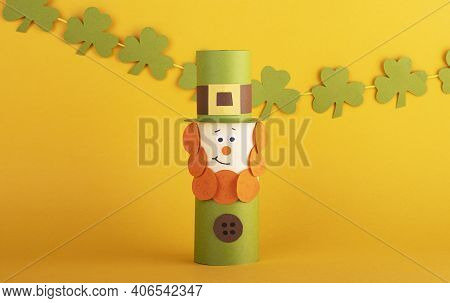 Leprechaun Made Of Handmade Paper With Green Four-leaf Clover On The Background. Cultural And Religi
