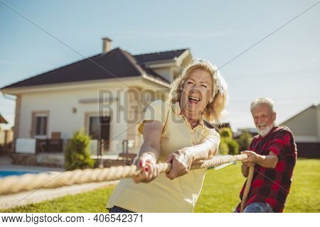 Senior Couple Having Fun Playing Tug Of War Game, Spending Sunny Summer Day Outdoors; Group Of Elder