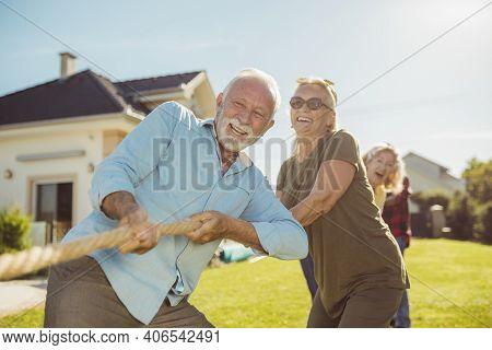 Senior People Having Fun Playing Tug Of War, Spending Sunny Summer Day Outdoors; Group Of Elderly Fr
