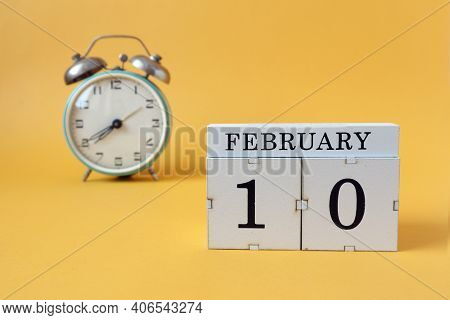 Calendar For February 10: Cubes With The Number 10 And The Name Of The Month, Alarm Clock On A Yello