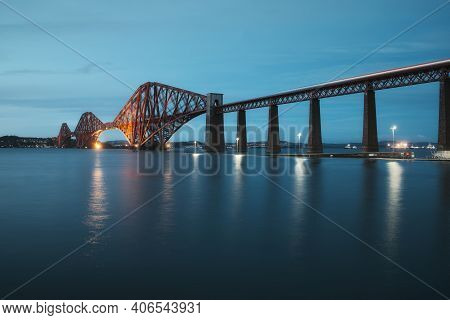 View Of Forth Rail Bridge At Night And And The Glow Trail Of A Moving Train Over The Sea. View Of Fo