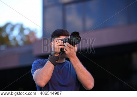Photographer Taking Picture With Professional Camera On City Street In Evening