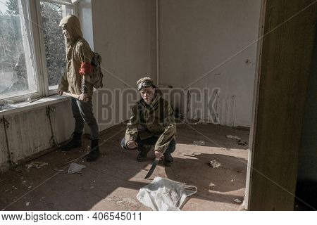 Boys Standing In An Abandoned Building. Wandering Boy. Man In A Protective Cloak With A Hood. Post A
