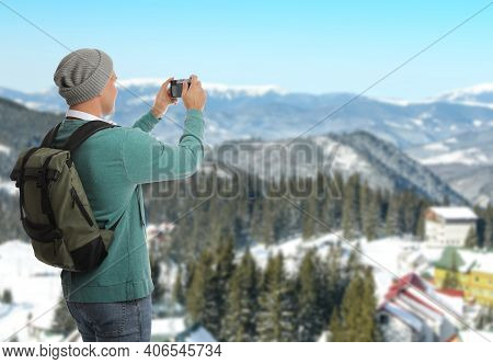 Tourist With Travel Backpack Taking Photo In Mountains During Vacation Trip