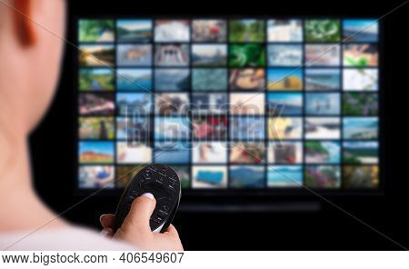 Online Multimedia Video Concept On Tv Set In Dark Room. Woman Watching Online Tv With Remote Control