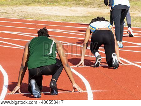 Rear View Of Female Sprinters On Their Mark Ready To Start Their Sprint Running Race Wearing Spandex