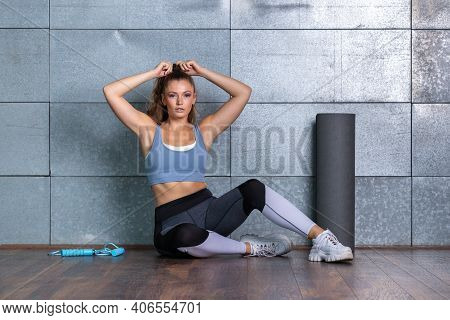 Young Fit Woman Sitting On Wooden Floor And Tie Her Hair To A Ponytail In Front Of A Metal Backgroun