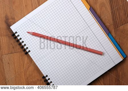 Open Tear-off Notepad For Notes Squared Sheets With A Red Pencil On A Wooden Background Close-up