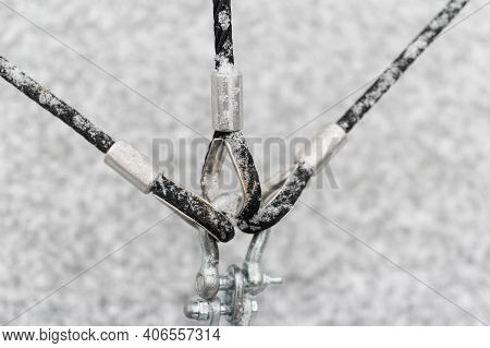 Three Metal Cables And Hooks Holding Steady A Structure