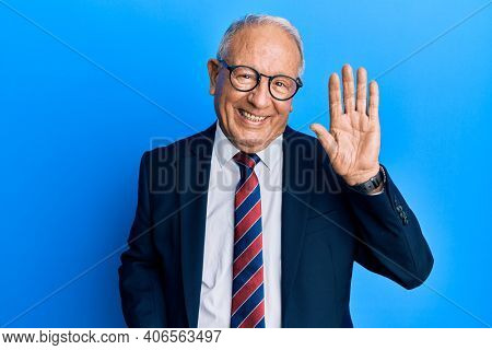 Senior caucasian man wearing business suit and tie waiving saying hello happy and smiling, friendly welcome gesture