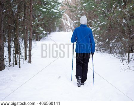 Ordinary Woman In Blue Warm Sportwear Does Nordic Walking On The Snow In The Parkland In Winter Outd