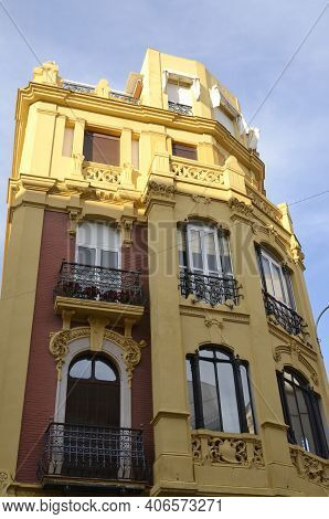 Building With Typical Ocher And Crimson Red Colors Of Seville Architecture, Andalusia, Spain.