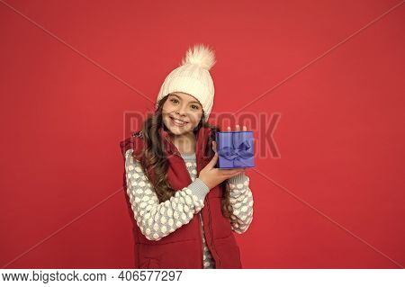 Make Pleasant Things. Happy Kid In Winter Outfit Red Background. New Year Is Coming. Small Gift Box