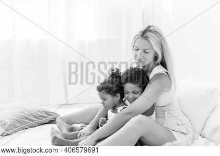 Young Caucasian Blond Mother Plays, Lies On White Bed With African American Daughter Son. Happy Mult