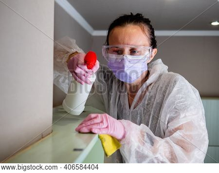 Pest Control And Unsanitary Conditions. A Worker In A Protective Suit Cleans The Shelves In The Kitc