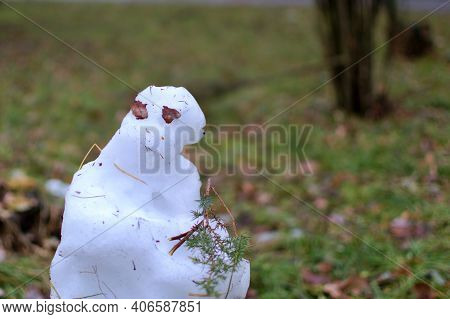 Melted Snowman On Blurred Background Of Green Park In Spring