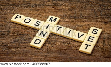 positive mindset crossword in ivory letter tiles against rustic wood, positivity, lifestyle and personal development concept