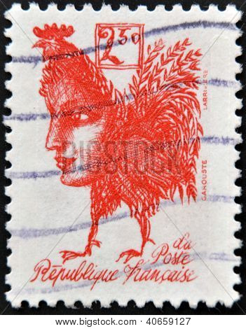 A stamp printed in France shows a gallic rooster with the face of Marianne