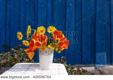 A Bouquet Of Spring Flowers In A White Vase On A Blue Wooden Background.