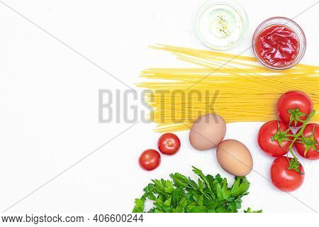 Spaghetti And Tomatoes On A White Background . Ingredients For Cooking Spaghetti. White Background.