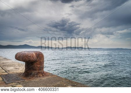 Single, Old And Rusty Mooring Bollard On The Pier With A View On Adriatic Sea And Dramatic Sky In Za