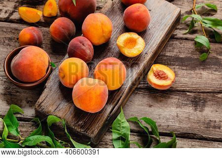 Peaches With Leaves On A Wooden Board With Peach In Halves. Flat Lay Composition With Ripe Juicy Pea