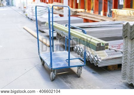 Trolley In A Hardware Store With Building Materials. Warehouse Large Storage. Shopping Trolley Cart