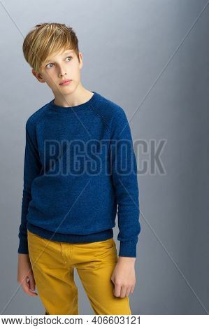 Portrait Of Stylish Teenage Boy. Handsome Teenager Wearing Blue Pullover And Yellow Pants Posing In