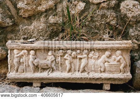 Close-up Of A Flower Pot With A Bas-relief Depicting People And Animals Against A Stone Wall And A G