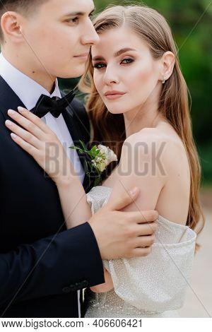 Beautiful, Gentle And Happy Bride And Groom Hugging