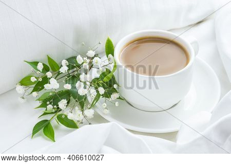 Cup Of Coffee On The Bed With White Flowers And Green Leaves. White Bed Linen, Good Morning Concept.