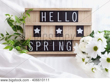 Hello Spring - Text On Wooden Board With White Flowers And Green Leaves On White Bed Linen. Springti