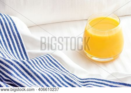 Glass Of Orange Juice On Bed With White Linen And Blue Bedspread. Good Morning Concept.