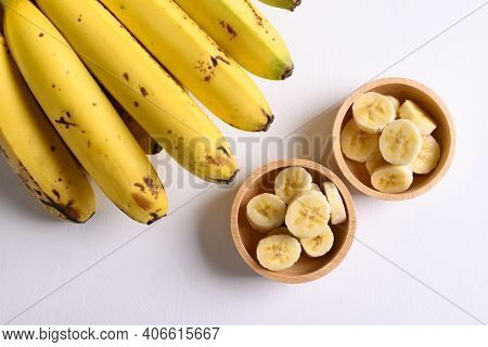 Sliced Ripe Banana Fruit In A Wooden Bowl And Bunch Of Ripe Banana On White Backgrount, Top View