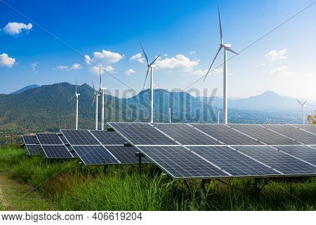 Photovoltaic Modules Solar Power Plant With Wind Turbines Against Mountains Landscape Against Blue S