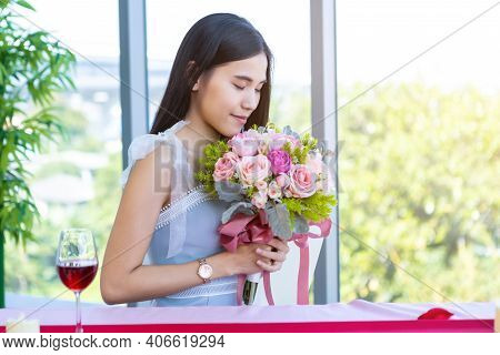 Valentine\'s Day Concept, Happy Of Smiling Asian Young Female Sitting At A Table Food Holding A Bouq