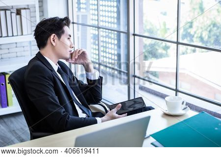Happy Relax Mood Asian Young Businessman Working A Tablet Wear A Business Suit Looking At The Window