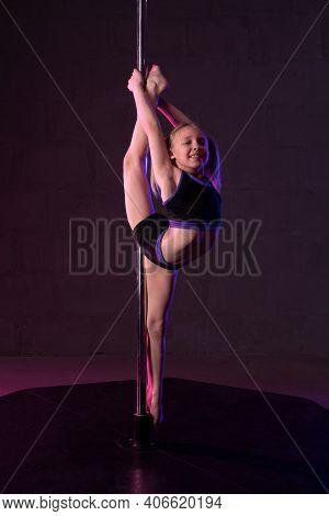 Flexible Girl Performing Gymnastic Exercise Near Pole