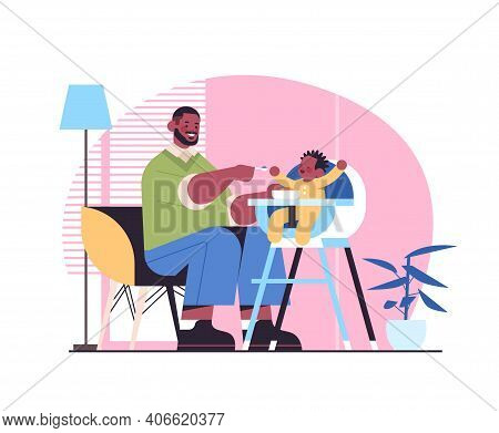 African American Father Feeding His Little Son On Kids Eating Chair Fatherhood Parenting Concept Dad