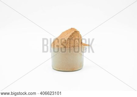 Whey Protein Powder On White Background. Plastic Measuring Dietary Spoon And Heap Of Chocolate Shake