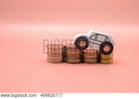 White Toy Car On Pile Money Stack Coins Growth On Pink Background. Miniature Automobile Model And Bu