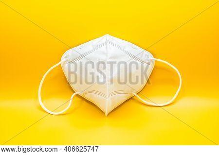 Anti-pollution Mask On Orange Background. Protection White Medical Face Mask For Epidemic Coronaviru