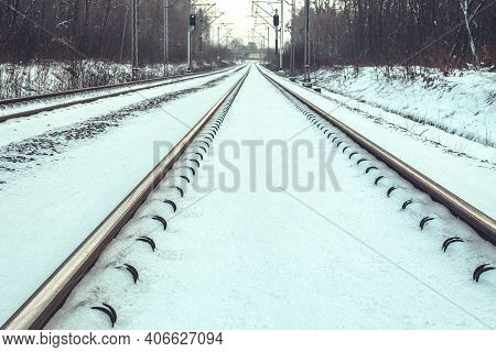 The Rails Are Covered With Snow In The Winter Forest. Rails From The Driver's Cab