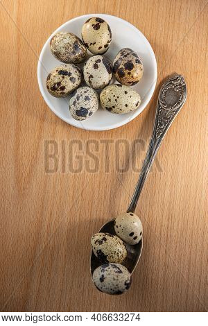 Quail Eggs In A Spoon On A Table Surface Indoors. Food Ingredient.
