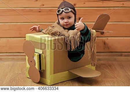Funny Child Pilot Flying A Cardboard Box. Child Dream. Aircraft Construction, Education. Thumbs Up