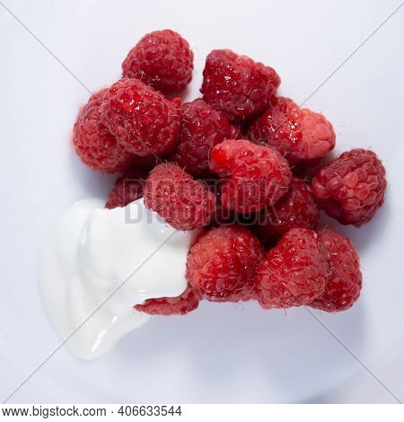 Red Raspberries Poured With Sour Cream In A White Dish. Dessert.