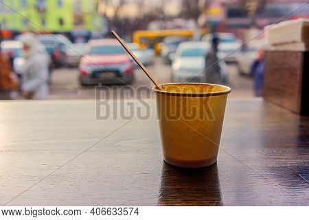 Dirty Empty Disposable Paper Cup From Under Coffee Stands On A Wooden Table Against The Background O